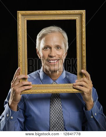 Caucasian middle aged businessman smiling through empty picture frame in front of face.
