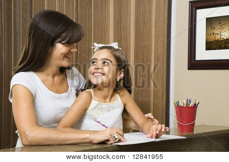 Hispanic mother helping daughter making eye contact and working on homework.