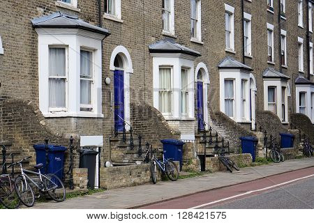 CAMBRIDGE, UK - AUGUST 8: Bicycles and blue recycling wheelie bins sit outside the front doors of a row of terraced houses in a residential street with a bike lane in Cambridge, England on August 8, 2015.