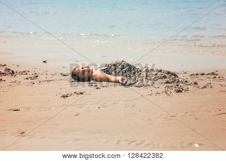 Child enjoying on beach cover in sand, beautiful sunny day