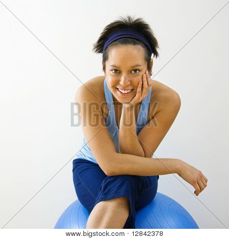 Portrait of young Woman sitting on Fitness Balance Ball lächelnd.