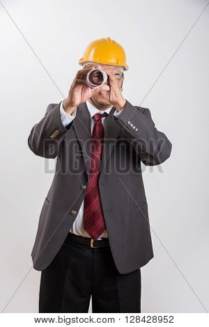 indian businessman holding a blueprint, wearing yellow hard hat, isolated over white background, indian architect with yellow hat and blue print ** Note: Shallow depth of field