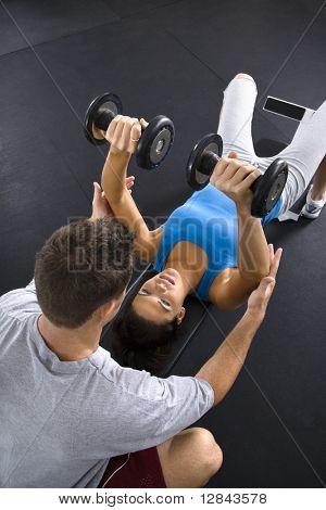 Hombre a mujer ayudando a levantar pesas en el gimnasio.