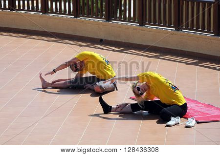 HERAKLION, CRETE ISLAND, GREECE - MAY 05, 2010: Two girls exercise in the open air
