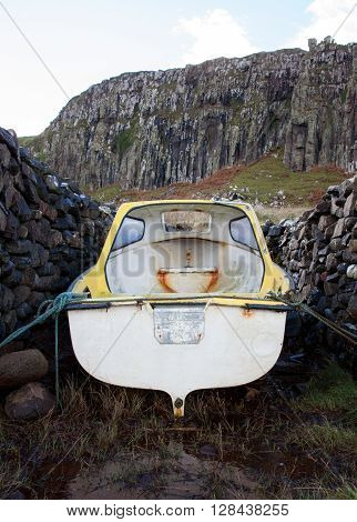 Small boat in between stone walls on Isle of Skye