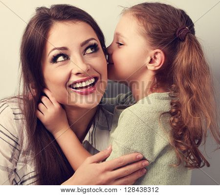 Happy Cute Kid Girl Whispering The Secret To Her Laughing Happy Mother In Ear With Fun Face. Closeup