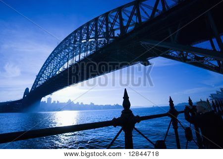Low angle view of Sydney Harbour Bridge at dusk with harbour and distant Sydney skyline, Australia.