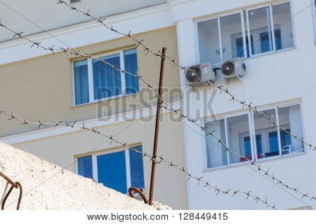 Apartment Building Window Is Out Of Focus Behind Barbed Wire