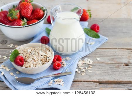 Rolled oats in a bowl with berries and milk on wood