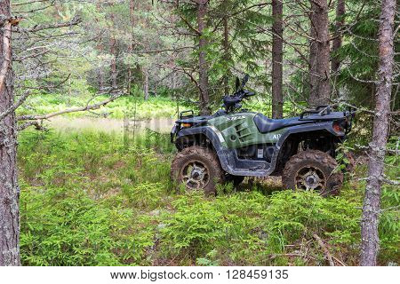 NOVGOROD REGION RUSSIA - JULY 9 2015: The modern quad bike parked at the forest in summer day