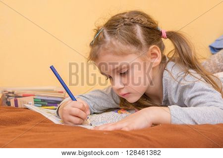 Little Girl Draws A Hard Lying On His Stomach With A Pencil On Paper