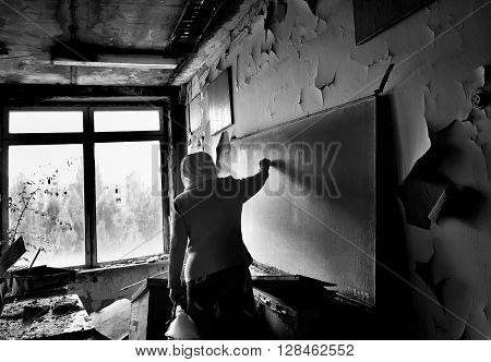 Pripyat, Ukraine - May 9, 2011: Evacuated teacher writes on the blackboard in her former classroom in abandoned school in Pripyat town in Chernobyl Exclusion Zone, place of Chernobyl nuclear disaster.