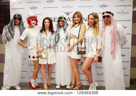 RUSSIA, MOSCOW - JUN 12, 2015: Group of young people in white clothes stands in front of poster of Sensation Wicked Wonderland at Olympiysky sports complex.