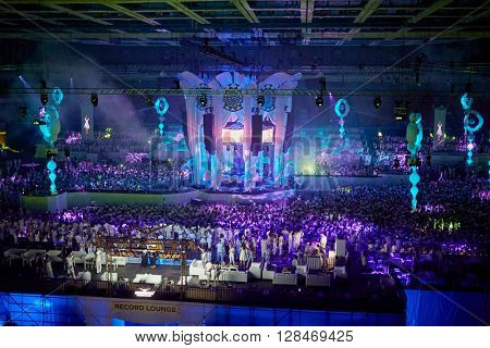 RUSSIA, MOSCOW - JUN 12, 2015: Dancing people on dance floor around central stage and grandstands at Sensation Wicked Wonderland show at Olympiysky sports complex.