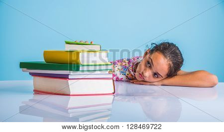 education and home concept - stressed student girl with books, indian girl child tired of studying or doing homework, asian girl studying and stressed, with globe toy and coffee mug