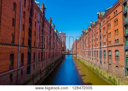 Large river canal in the middle of the city, building on the sides made of bricks. Low water