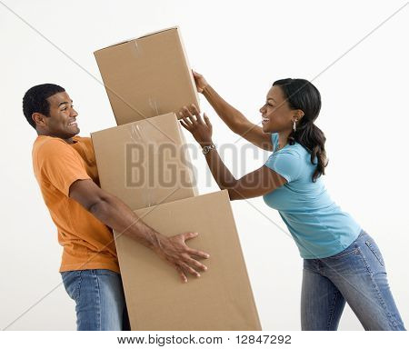 African American woman placing boxes on large stack man is holding.