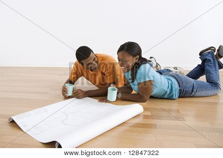 African American male and female couple lying on floor looking at architectural  blueprints.