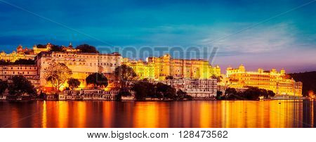 Vintage retro effect filtered hipster style image of panorama of famous romantic luxury Rajasthan indian tourist landmark - Udaipur City Palace in the evening - panoramic view. Udaipur, India