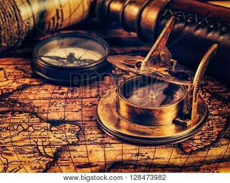 Travel geography navigation concept background - vintage retro effect filtered hipster style image of old vintage retro compass with sundial and spyglass on ancient world map with copyspace