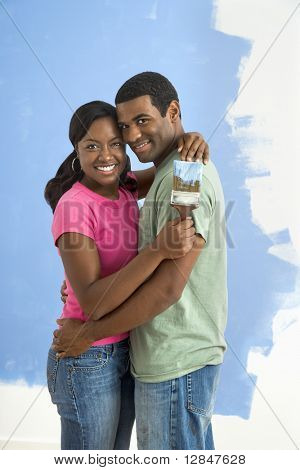 African American couple standing together hugging in front of half-painted wall and smiling at viewer.
