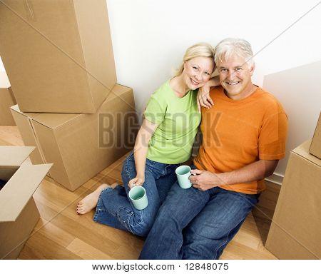 Aged Couple sitzen auf Boden unter Kartonagen Umzugskartons mit Kaffee.