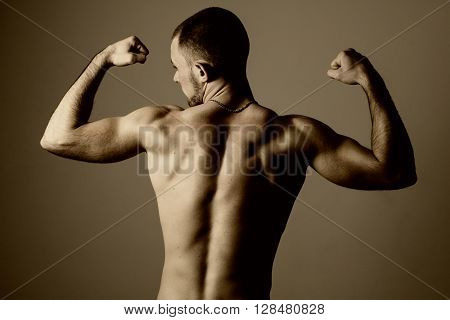 Portrait of a handsome muscular young man from the back. Shot in a studio. Toned image