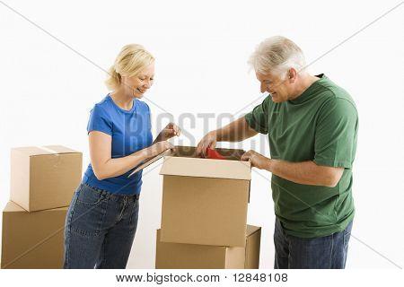 Пожилой пара упаковку или распаковку движущиеся коробки.