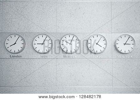 Five wall clocks showing time in different capitals of the world.