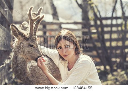 Young Beautiful Woman Hugging Animal Roe Deer In The Sunshine