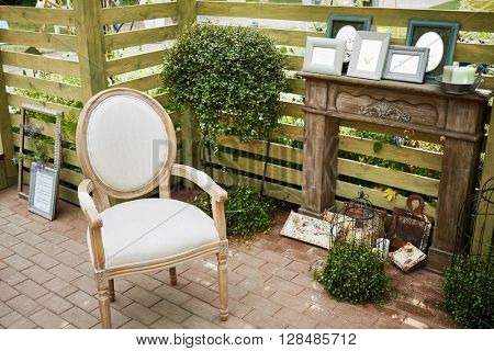 Wooden alcove with old armchair and different old things in park.