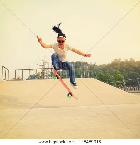 young skateboarding woman practice ollie at skatepark
