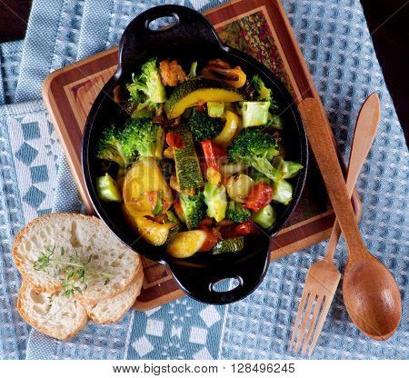 Homemade Colorful Vegetables Ragout with Zucchini Carrots Broccoli Leek and Red Bell Pepper in Black Iron Stewpot with Wooden Spoon and Fork and Bread closeup on Blue Napkin. Top View