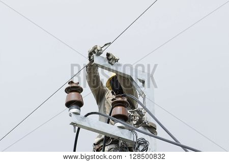 One electrician climbing on electric poer pole is repairing electrical power system for normal working. Closed-up view.