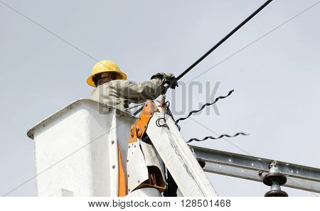 One technician is installing new cables on an electric pole from lift bucket. Close-up view.