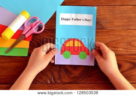 Child holds a card in his hand. Greeting card Happy father's day. Paper sheets, scissors, glue. How to make a greeting card father's day
