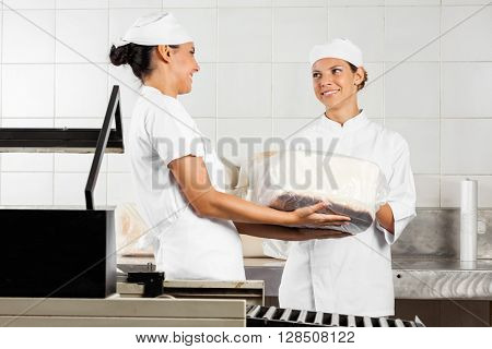 Young Baker's Looking At Each Other While Packing Breads