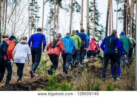 Ekaterinburg Russia - April 24 2016: large group of athletes runners running uphill in woods during a Mountain marathon