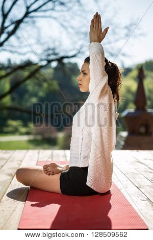 Peaceful girl is engaged in yoga on the wooden terrace on the nature background. She sits sideways in the lotus pose on the red yoga mat and stretches her connected hands over the head. She wears black shorts and white cardigan.