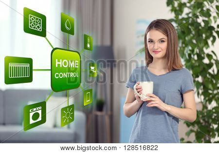 Smart home control concept. Young woman in living room