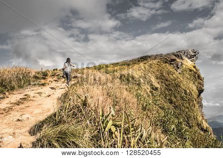 Woman walking above hill. Concept of goal setting and strive to accomplishment the goals.