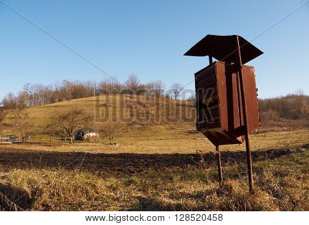Old common mailbox in countryside with the hill and trees on the background