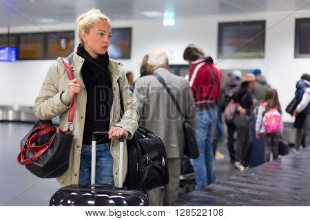 Casually dressed young female traveller waiting in airport arrival terminal hall,  collecting her laggage . Blured background. Can also be used as railway, metro, bus station. ** Note: Soft Focus at 100%, best at smaller sizes