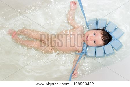 Baby girl swiming in the bath with special blue swiming mutch. Mother hands taking her head under water level