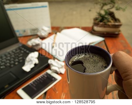 Man working on laptop and holding cup of black coffee for great ideas. Coffee with work and relax time. Freelance work Laptop computer phone and coffee.