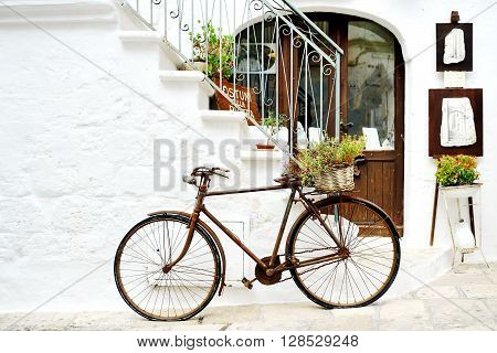 vintage rusty bicycle against a wall in white city Ostuni Apulia Italy. - artistic picture italian style concept