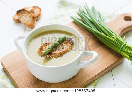 A white bowl of asparagus soup with asparagus spears and bread on top arranged on cutting board with chive