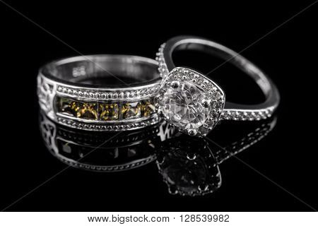 Silver or white gold engagement rings with yellow gems and diamonds on black glass background poster