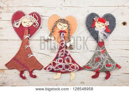Three sewn angel dolls on white wooden background