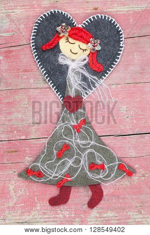 Sewn angel doll on pink wooden background